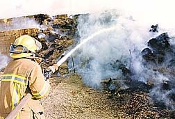 Firefighter Jim Asa sprays fire retardant on a hay bail that caught fire at the Northern Nevada Correctional Facility dairy farm on February 15, 2001. Photo credit Nevada Appeal.