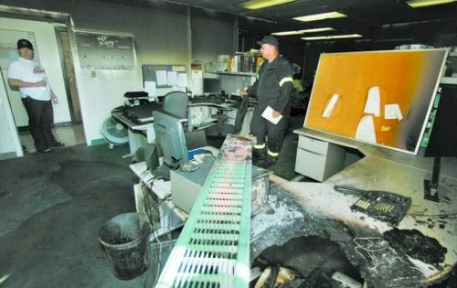 Click to enlarge - Carson City fire department investigator Duane Lemons, center, looks through the detectives' unit at the Carson City Sheriff's office after a fire on Saturday afternoon. The message light on the phone, seen melted in the right lower corner of the photo, was blinking.  Photo credit - Brad Horn/Nevada Appeal