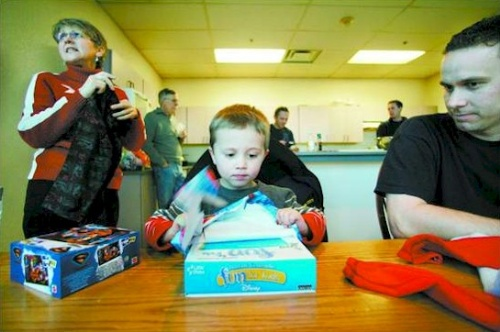 Click to enlarge - Carson City firefighter Bryon Hunt watches his 3-year-old son Tyler open a present while Meri Gscheidle, Bryon's mother, puts away Tyler's other gifts on Monday afternoon.  Photo credit - Brad Horn/Nevada Appeal
