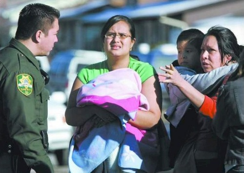 Carson City Sheriff's Deputy Rick Duarte talks with Silvia Ramos, right, and her daughter Maria Ramos, 15, who is holding a one-month-old infant, after a fire forced them from their Woodside Drive apartment Friday afternoon.  Photo credit - Cathleen Allison/Nevada Appeal