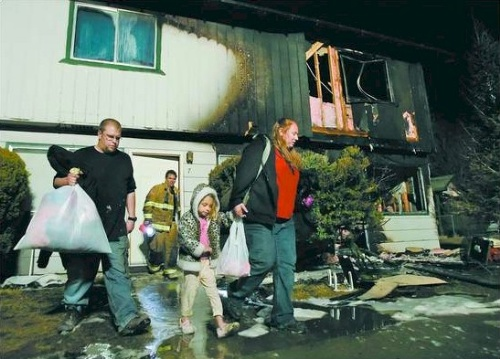 Heather Holt, right, her husband Jeremy, left, and 5-year-old daughter Makeyla leave their home with what they could carry after fire gutted a neighbors apartment in east Carson City the night of March 7, 2007. Firefighters were forced to tear down the ceilings in Holt's townhome to make sure the fire hadn't gone into the attic.  Photo credit - Chad Lundquist/Nevada Appeal