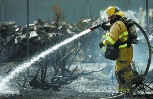 Click to enlarge - A Carson City firefighter works to extinguish a brush fire at Villa Sierra mobile home park in the 4900 block of Highway 50 East on Monday. One home was damaged and one-quarter of an acre was burned.  Photo credit - Chad Lundquist/Nevada Appeal