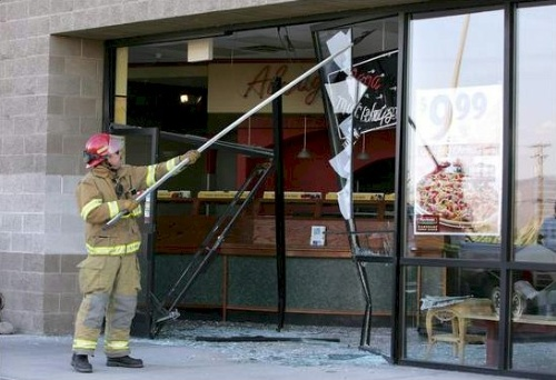 Carson City Fire Capt. Eric Bero knocks down loose glass at Papa Murphy's, in South Carson City on July 12, 2007, after a woman drove into the store front nearly hitting several employees and customers.  Photo credit - Cathleen Allison/Nevada Appeal