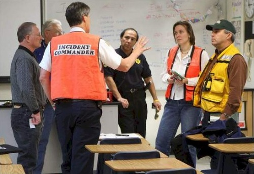 Carson City Fire Departement Battalion Chief Dan Shirey, center, talks with city, school and EPA officials Wednesday afternoon, February 6, 2008 following a mercury spill at Carson High School. 22 students and a teacher were quarentined for several hours.  Photo credit - Cathleen Allison/Nevada Appeal