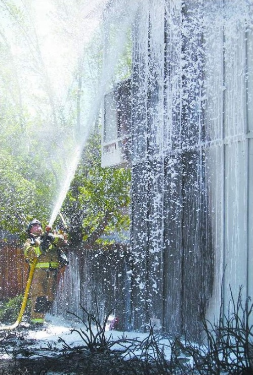 A Carson City firefighter sprays foam on an Edmonds Drive apartment fire Tuesday afternoon, April 29, 2008. Fire officials say tenants with fire extinguishers helped limit the damage.  Photo credit - Cathleen Allison/Nevada Appeal