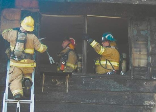 Click to enlarge - Carson City firefighters work to extinguish flames that crept into the attic and siding of a complex on David Street. Four families were displaced.  Photo credit - F.T. Norton/Nevada Appeal