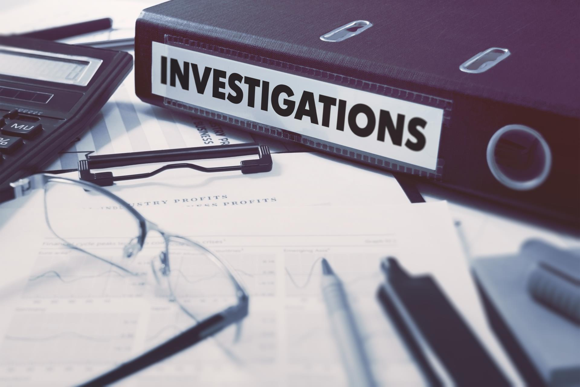 Displays a binder that says investigations