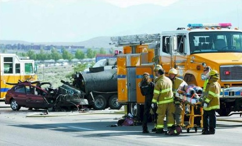 Click to enlarge - Rescue personnel work to prep one of the victims for airlift from the scene of an accident at South Carson Street and Snyder Avenue on Monday. The Dodge Neon traveling northbound collided with a commercial truck and trailer carrying pavement sealer after it attempted to cross the car's path. Three children were seriously injured. Photo credit - Chad Lundquist/Nevada Appeal.