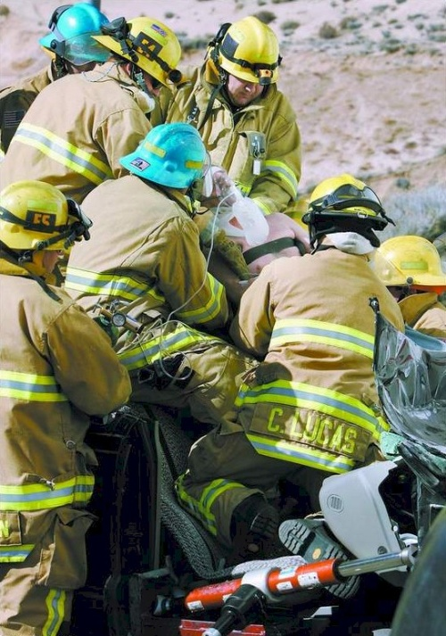 Firefighters from Carson City and Tahoe-Douglas fire departments work to remove 54-year-old David Ryan, of Zephyr Cove, from his vehicle February 12, 2006 on Highway 50 West, following a collision into a parked trailer.  Photo credit - Chad Lundquist/Nevada Appeal.