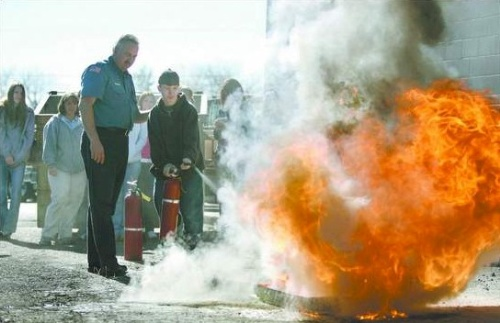 Click to enlarge - Tom Tarulli, public-education instructor for the Carson City Fire Department, shows Kris Cossette, 16, how to operate a fire extinguisher Tuesday morning. Tarulli uses a mixture of gasoline and diesel to teach a group of Silver State Charter High School students about fire safety as part of the SERT program that includes first-aid and CPR training.  Photo credit - Cathleen Allison/Nevada Appeal.