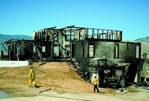 Carson City firefighters and inspectors walk through the three-story home that was destroyed on Conte Drive in southeast Carson City August 11, 2006. The house was under construction at the time of the fire.  Photo credit Brad Horn/Nevada Appeal