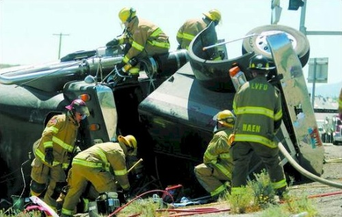 Click to enlarge - Carson City firefighters work to free Shane Bikman, of Idaho Falls, Idaho, after he flipped his tractor trailer at the corner of Highway 50 West and U.S. 395 on Thursday afternoon.  Photo credit Brad Horn/Nevada Appeal