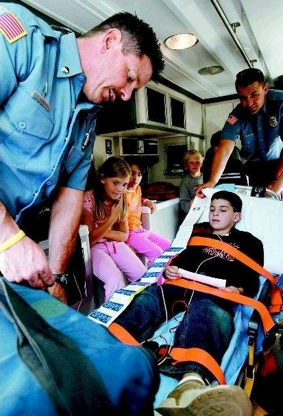Carson City Fire Department paramedics John Arneson, left, and Mike Santos, far right, demonstrate how everyday emergencies are handled in the back of an ambulance, with a little help from Andrew Adamson, 7, center, and his classmate from Mrs. Hickenbottom's second-grade class. Multiple agencies attended Wednesday's fire education day at Fritsch Elementary School.  Photo credit - Chad Lundquist/Nevada Appeal.