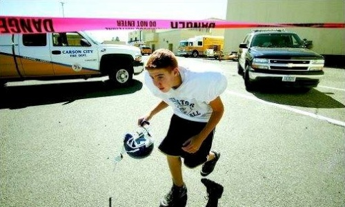 Kyle Whipple, 14, ducks under hazard tape after leaving the locker room at Carson High School. The school was closed Wednesday afternoon after it was reported that a nurse found a blood pressure unit that had been tampered with and leaked mercury.  Photo credit - Brad Horn/Nevada Appeal.