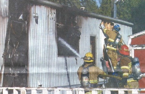 Click to enlarge -Carson City firefighters extinguish a mobile home fire Monday morning at the Safari Mobile Home Village.  Photo credit Cathleen Allison/Nevada Appeal