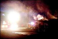Click to enlarge -Smoke billows from the Capitol City Trap Club on Arrowhead Drive Saturday night after turkey fryers caught fire, igniting the building. An elderly man suffered a cardiac arrest during the fire. Paramedics revived him with electric defibrillators. Photo credit - Nevada Appeal.