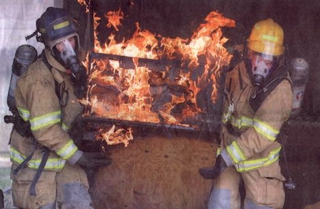 Click to enlarge - Carson City firefighters Tim Allen, left, and Jim Colatorti, right, carry out burning items from a garage on April 9, 2002.