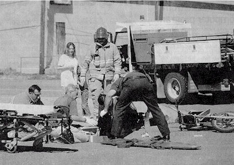 Click to enlarge - Carson City firefighters work on a 14-year-old boy who struck the side of a moving truck while riding his dirt bike along Edmonds at the Butti intersection on April 23, 2002.  The boy was transported to Carson-Tahoe Hospital where he was taken by CareFlight to Washoe Medical Center with leg and facial injuries.  Photo Credit Brian Corley/Nevada Appeal