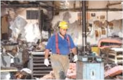 Click to enlarge - Fire Inspector Duane Lemons walks through the warehouse area of Cavallero Heating and Air Conditioning after a fire ripped through the office areas and caused smoke damage through the rest of the warehouse on June 17, 2002. The fire burned through to the second floor and the roof.  Photo credit Brian Corley/Nevada Appeal