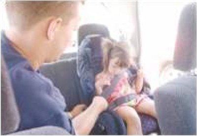 Bryon Hunt, left, installs a car seat properly as Maya Vasquez, 3, looks on July 20, 2002 at Western Nevada Community College.  Photo credit - Brian Corley/Nevada Appeal