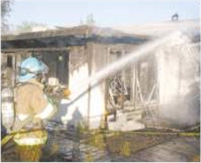 Carson City Firefighter Tim Dehaven puts water on a portion of the back of a house that burned July 29, 2002. The fire spread through the house an damaged the house next door.  Photo credit - Brian Corley/Nevada Appeal
