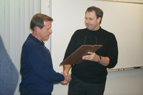 Click to enlarge - Fire Chief Lou Buckley presents retiring Captain Ed Kiewicz a service plaque at a retirement ceremony on December 12, 2002.  CCFD photo.