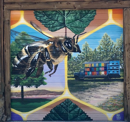 Mural was painted and designed by Erik Burke (b. 1978) who lives in Reno, NV and creates place-specific murals throughout the world. The Bee mural is Located at the Bee Magic Building in Mound House, Nevada (Erikburke.com)